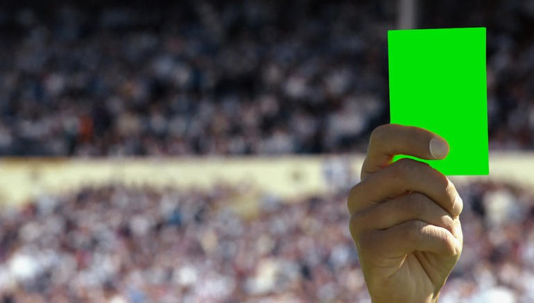 Hand holding up a yellow card --- Image by © Royalty-Free/Corbis